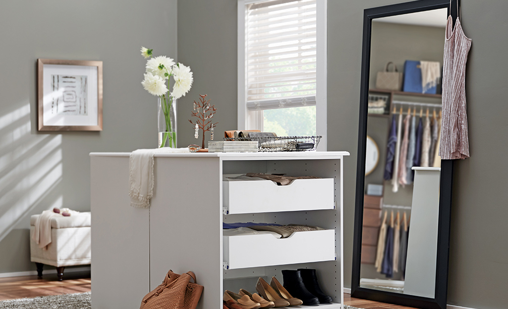 A full-length mirror against a wall and next to a storage island reflects racks of clothes in a walk-in closet.
