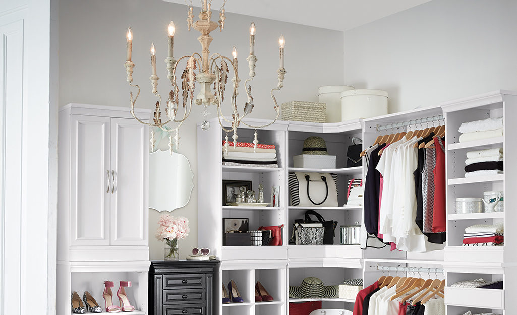 A candelabra-style chandelier hangs from the ceiling of a white walk-in closet with shelves and hanging clothes.