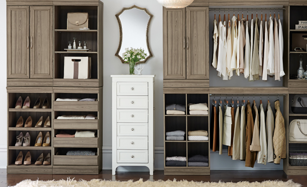 A mirror hangs above a small chest of drawers between two wall units of shelves, cabinets and clothing rods.