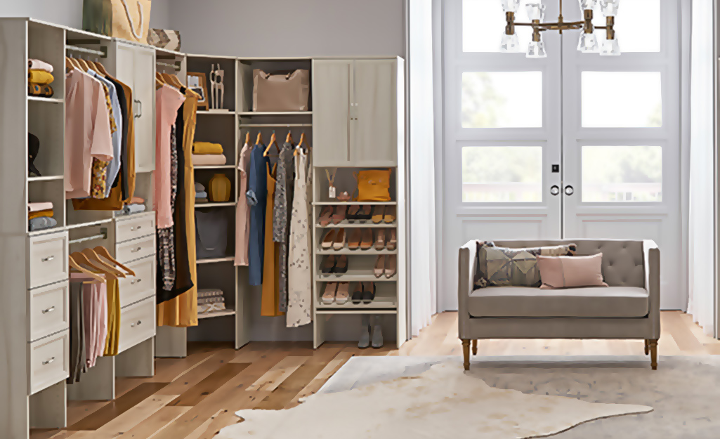 A small sofa sits on one side of a large walk-in closet, with hanging clothes, shelves and drawers on the other
