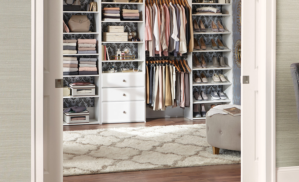 A patterned white rug covers the floor in front of the shelves, drawers and racks of a large walk-in closet.