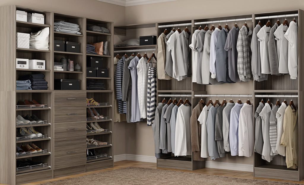 Clothes hang on rods on one side of a large gray walk-in closet, with shelves of shoes on the other.