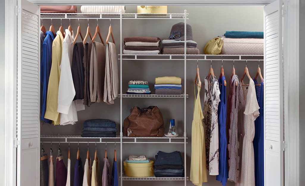 Clothes hang between white wire shelves in a closet system in a small walk-in closet.