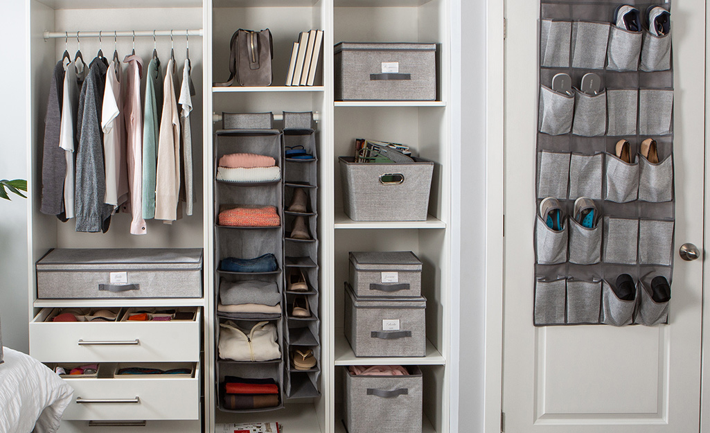 In a walk-in closet, gray bins, boxes and an over-the-door shoe rack provide storage options.