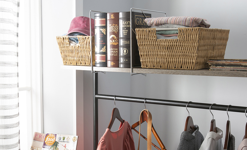 Brown baskets provide storage for folded items on a shelf above a clothing rod.