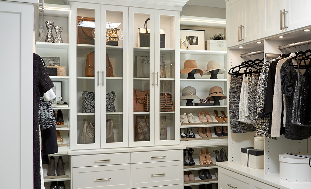 Handbags are on display behind glass doors in a white cabinet next to shelves of shoes in a walk-in closet.