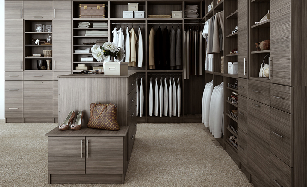 Shoes and a purse sit on an island in the middle of a large gray walk-in closet with wall units of drawers and shelves.