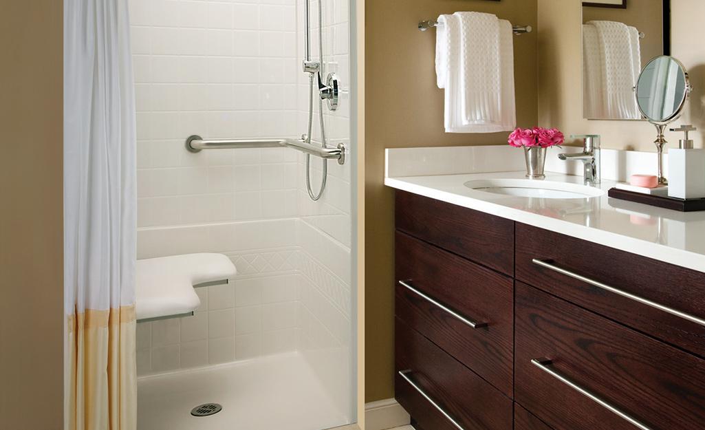 Một góc tắm vòi sen mở với băng ghế tích hợp, thanh vịn và đầu vòi sen linh hoạt.