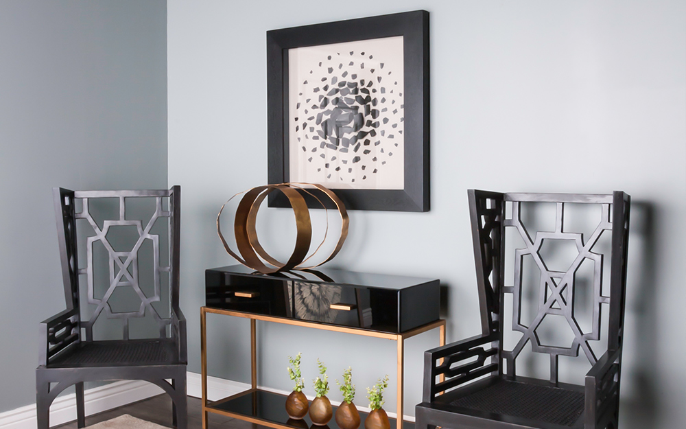 A shadow hung over a black console table and beside two black chairs as wall art