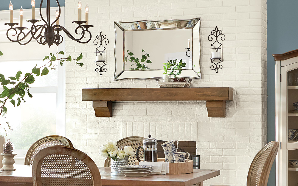 Matching sconces used as wall art on either side of a shelf with a large mirror.