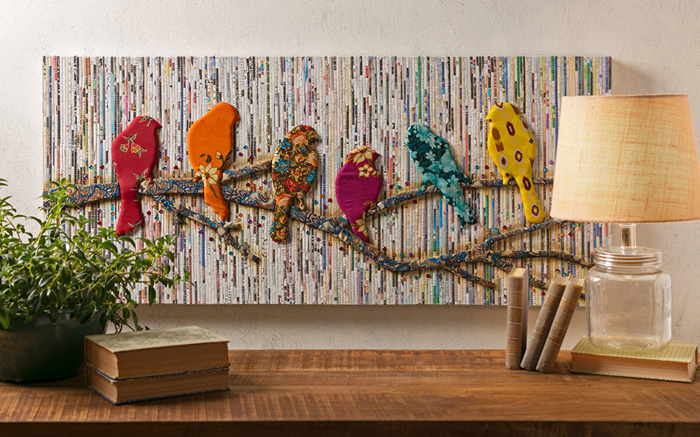 A textile featuring different colored birds hung as wall art.