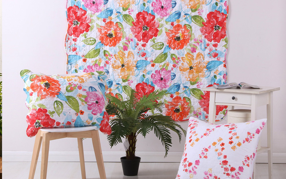 A floral quilt hung as wall art beside a chair with a matching pillow, a small plant, an end table and another pillow.