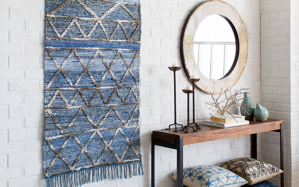 A woven rug hung on a wall as wall art.