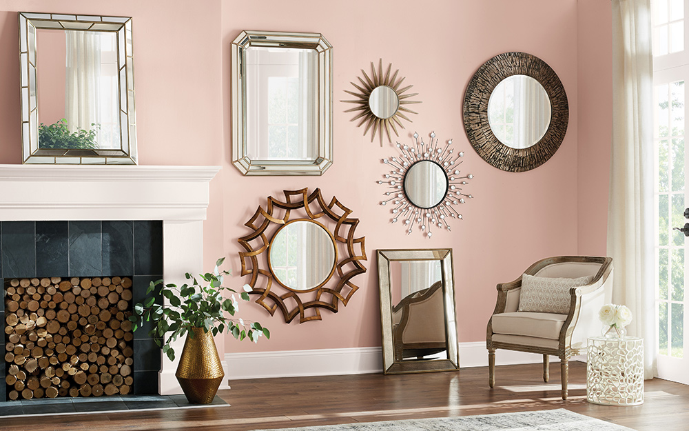 A group of mirrors in different sizes and styles used as wall art.
