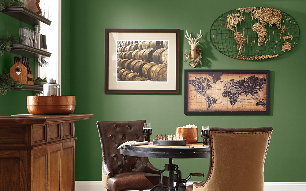 Framed maps used behind a table and two chairs as wall art.