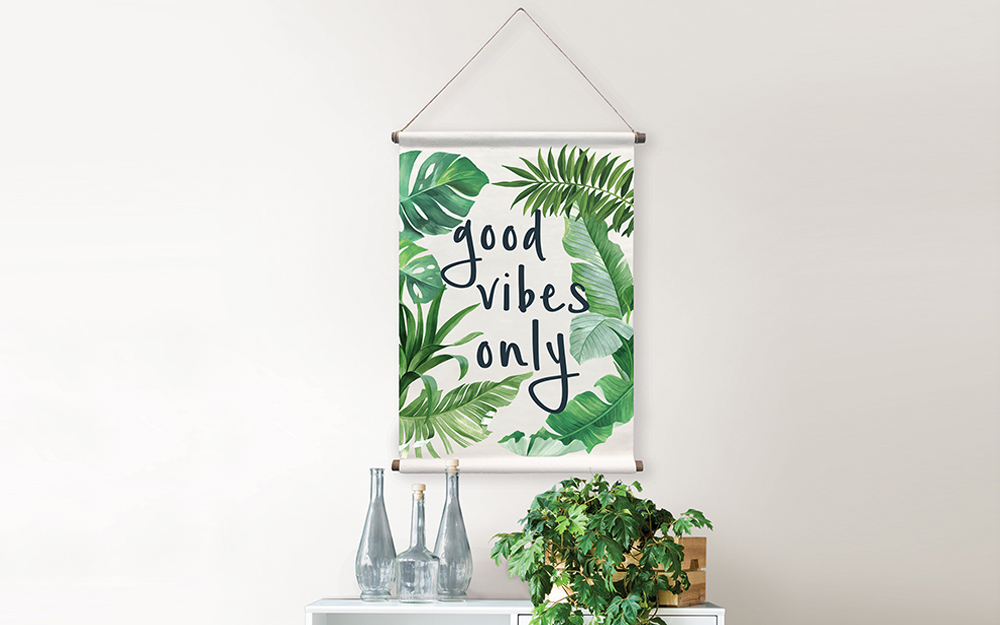 "A canvas reading ""good vibes only"" hanging from a rope and used as wall art."