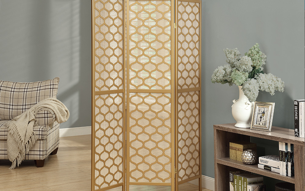 A patterned room divider used by a wall as wall art.