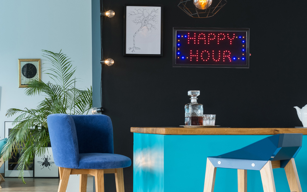 "A lighted, neon sign reading ""happy hour"" used as wall art over a home bar."