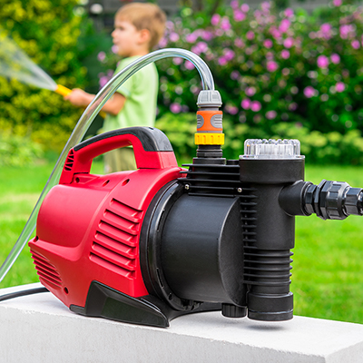 Boy spraying lawn in front of a red and black transfer pump.