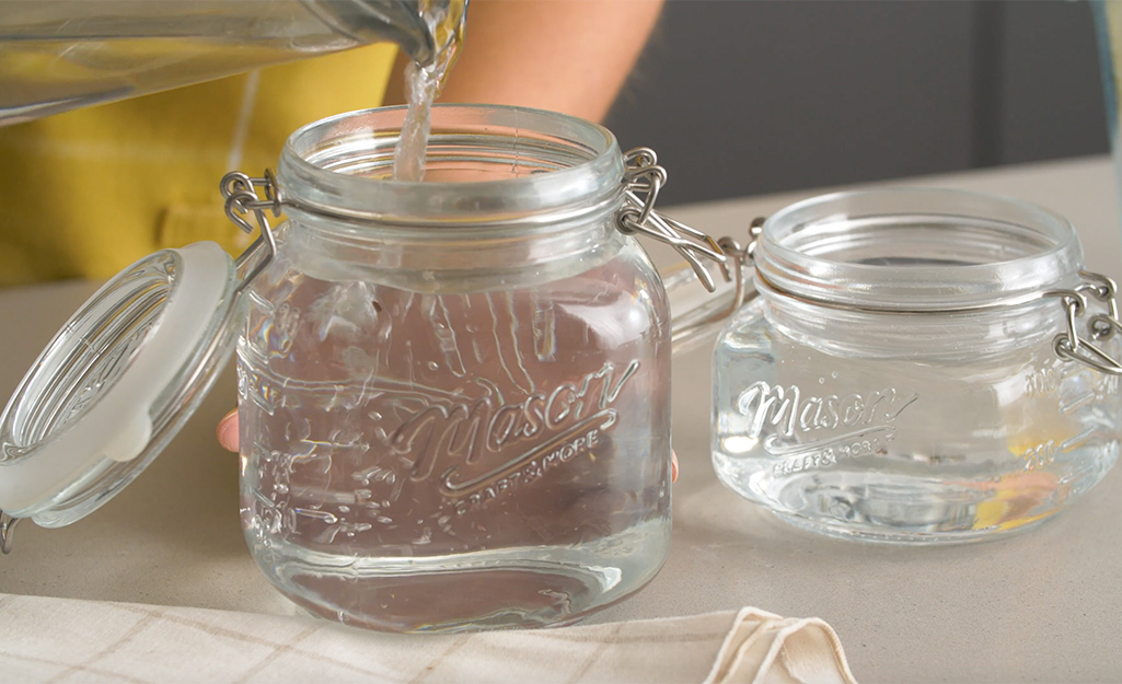 A woman pours water in her jars to prep.