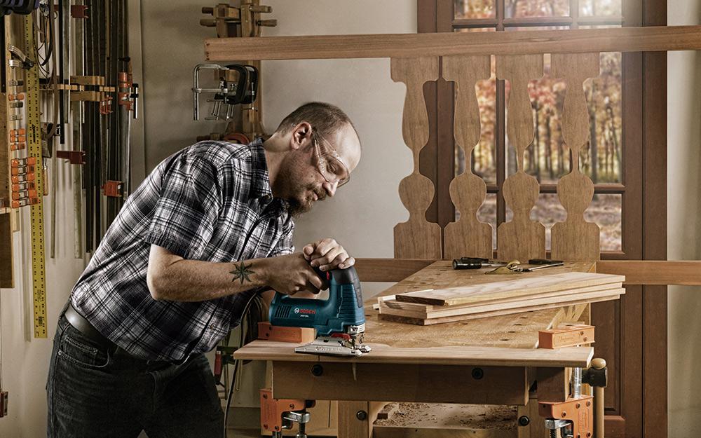 A man using a jigsaw on a plank of wood.