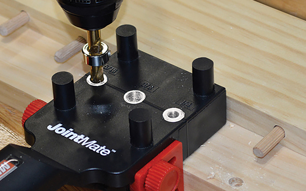 A dowel jig in use on a piece of light wood.