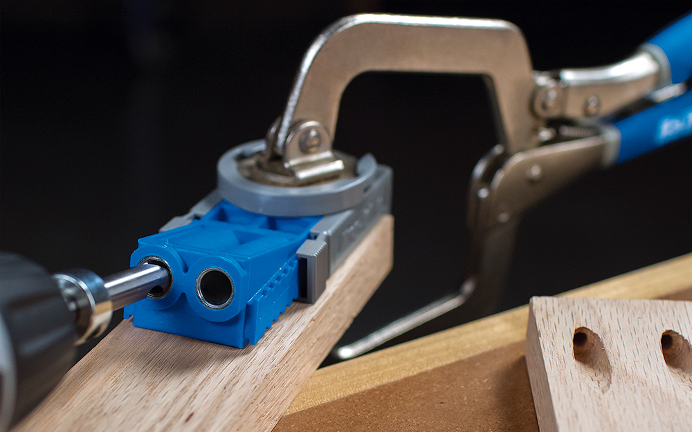 A drill jig being used on a piece of wood.
