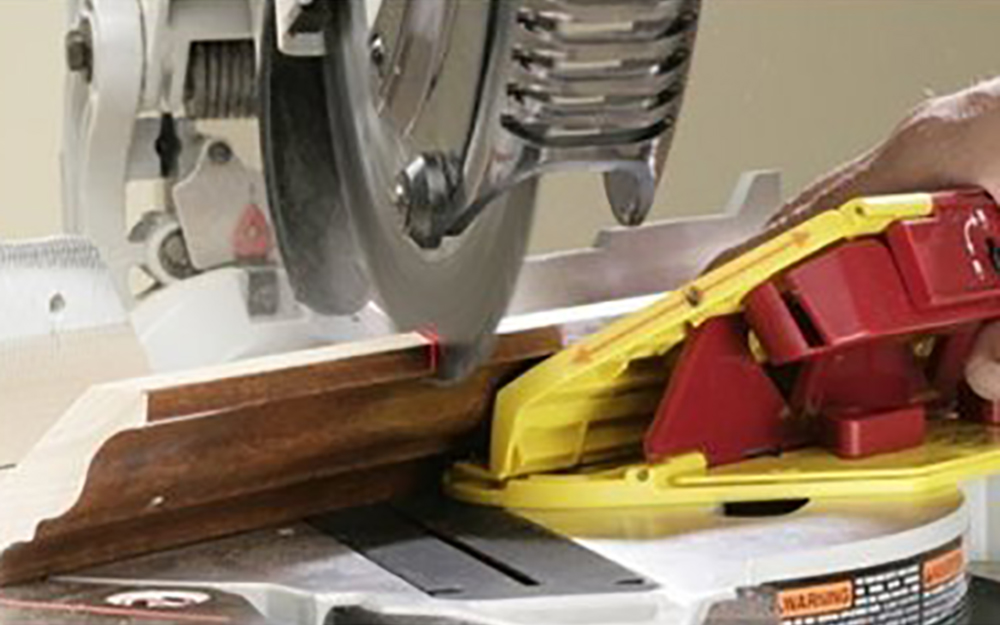 A miter jig in use on a piece of molding.