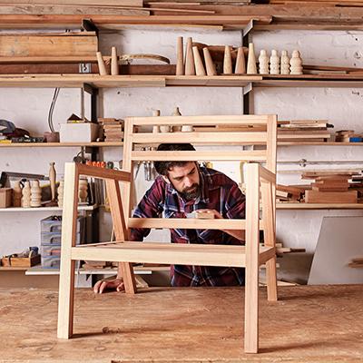A man sanding a wood chair using a woodworking jig.