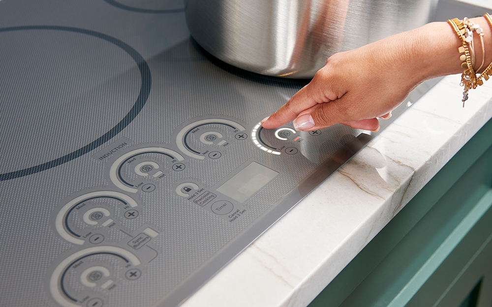 A person raising the temperature on an induction cooktop