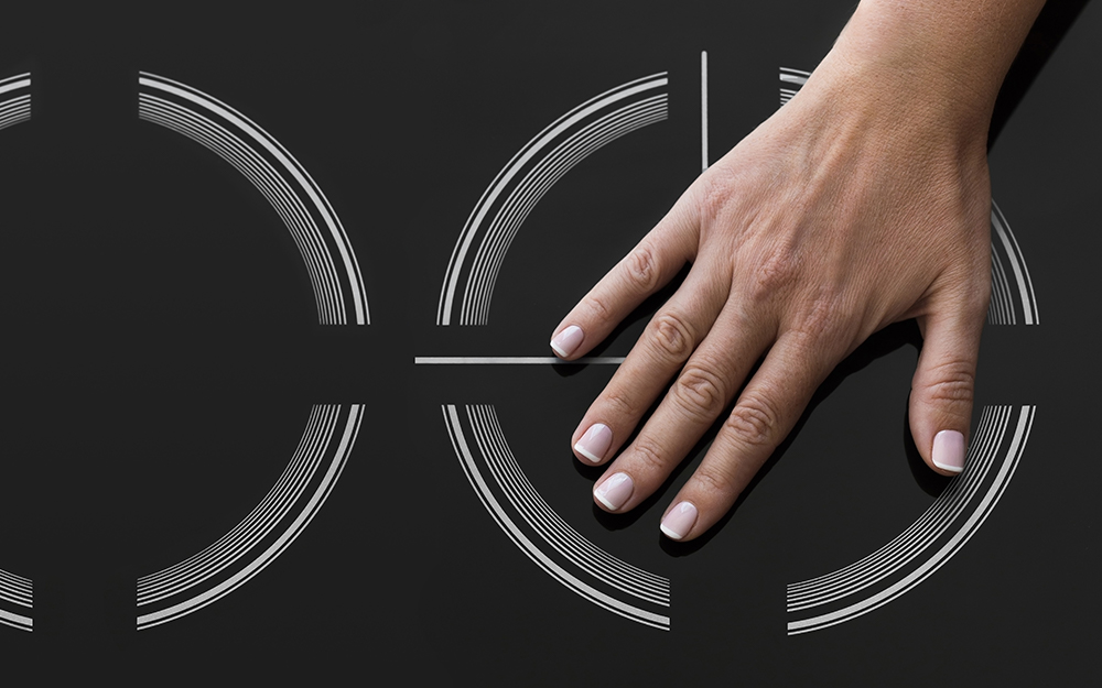 A person safely touching an induction cooktop while cool.