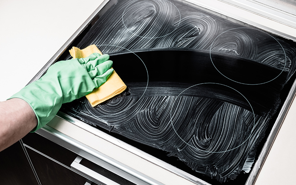 A person cleaning an induction cooktop