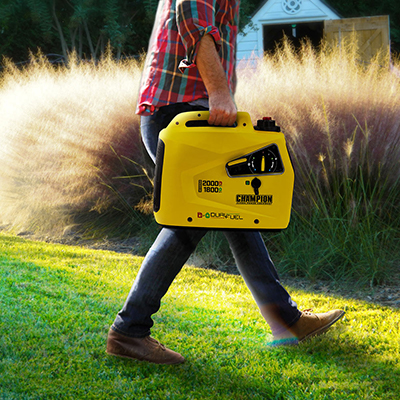 A person carries a yellow inverter generator.