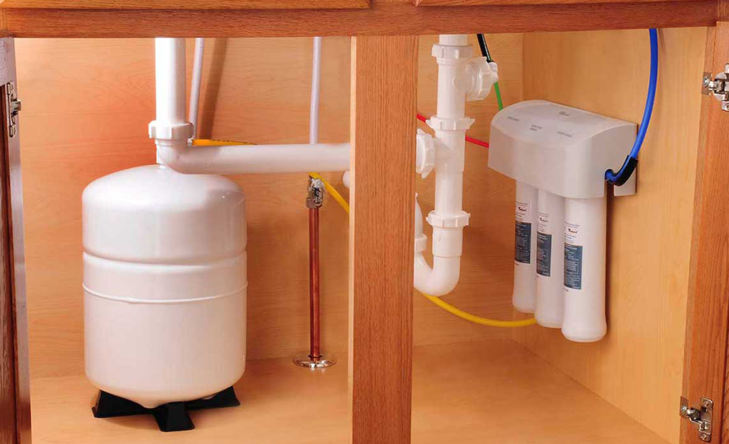 A reverse osmosis water treatment system installed underneath a kitchen sink.