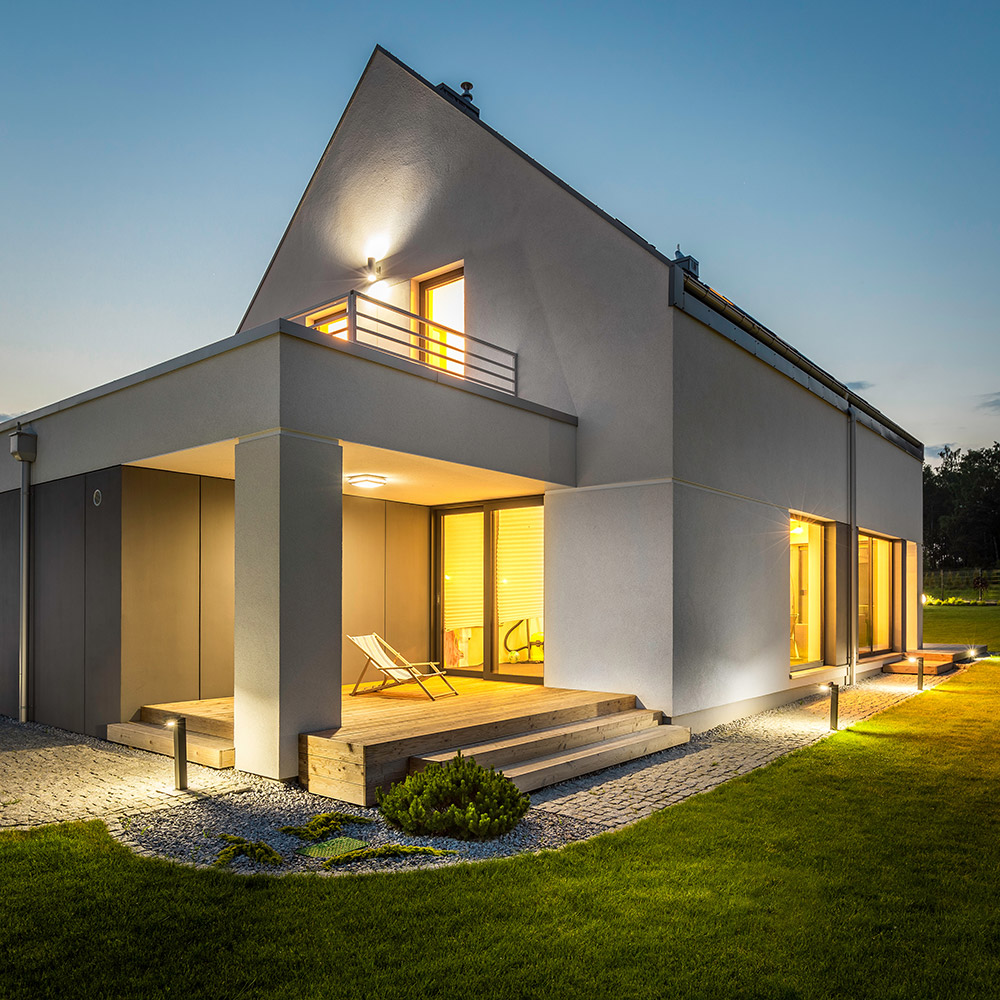 A modern house at night with lights turned on.