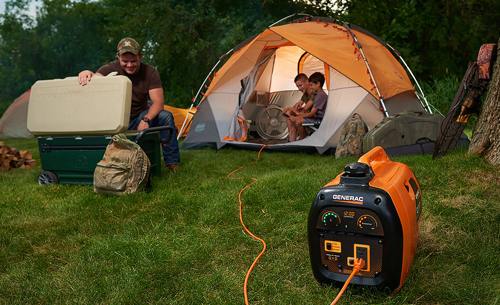 Small generator powering a light at a campsite.