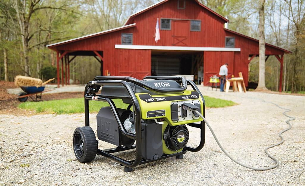 A portable generator on wheels sitting outside a red barn.