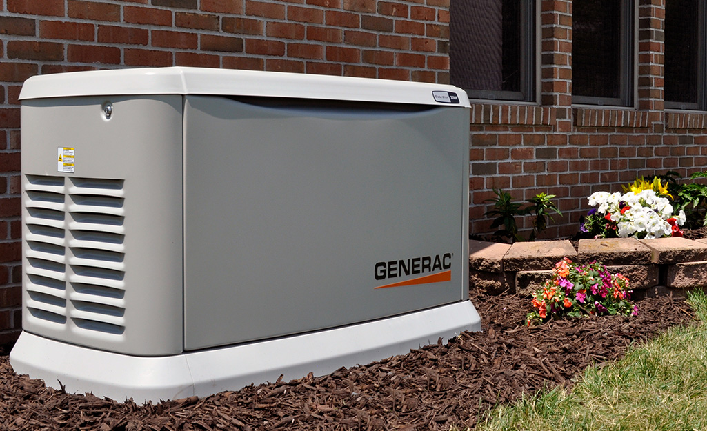 A home standby generator placed next to a brick house.
