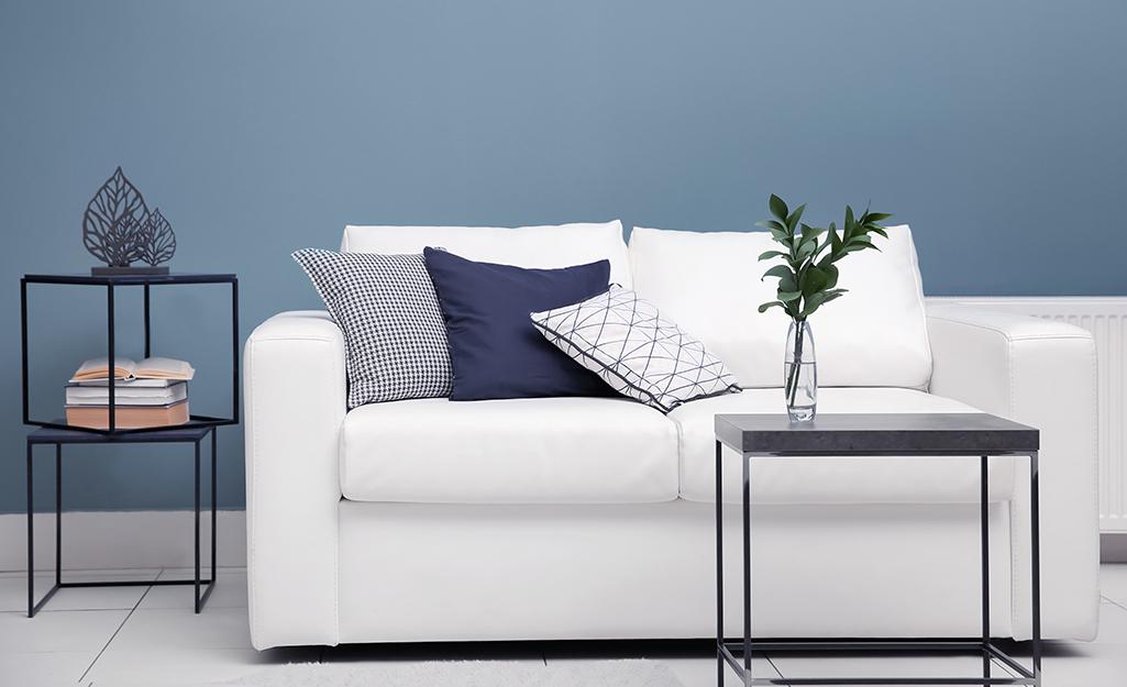 Một chiếc ghế sofa màu trắng đặt phía trước bức tường sơn màu xanh lam nhẹ nhàng.