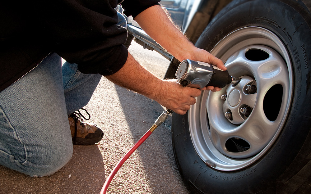 A person using an impact wrench on a tire.