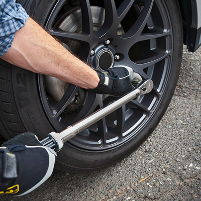 A person using a lug wrench on a tire.