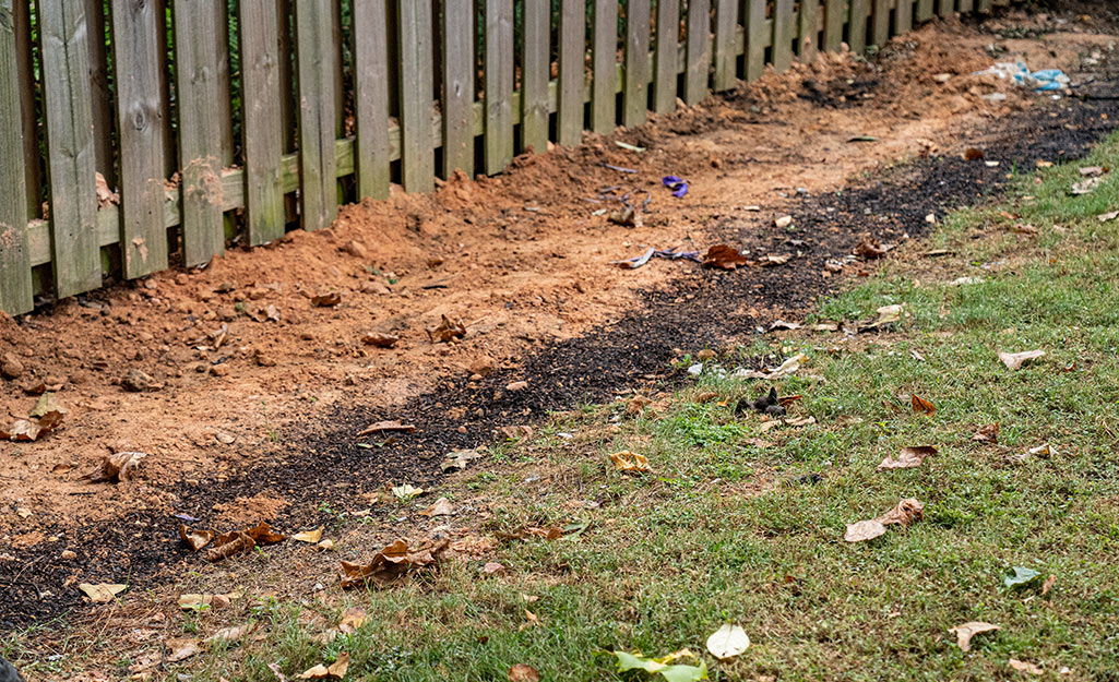 A covered French drain running near a fence.