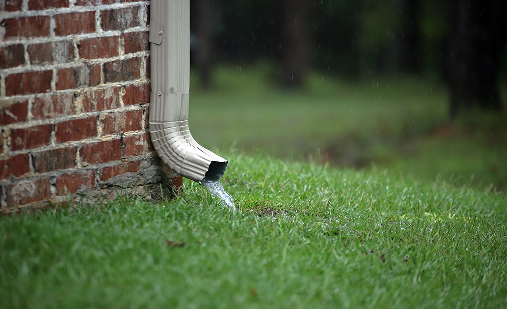 A downspout with water flowing through.