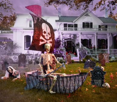 a skeleton sits upon a ship in yard full of outdoor halloween decorations