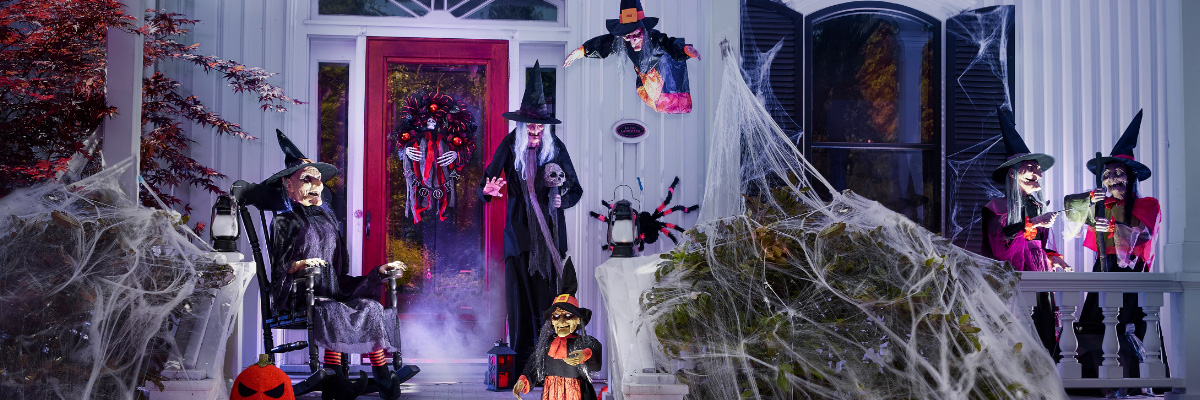 Withes dressed in black outside of a home decorated for Halloween