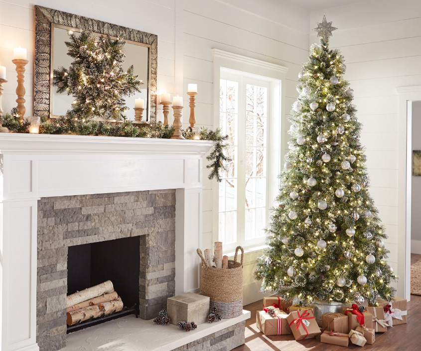 white fireplace with christmas garland wreath and candles