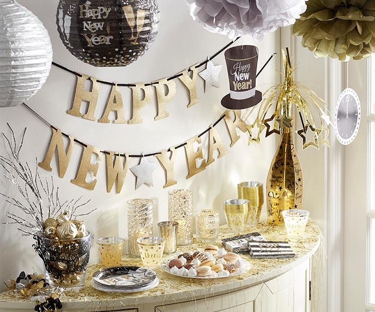 a gold happy new year banner is hung over a table of party treats and beverages