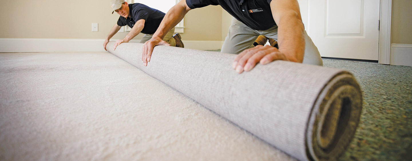 Two Men Installing New Roll Of Carpet