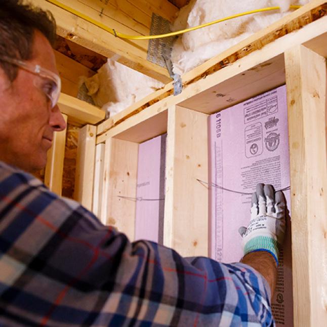 Man installing Foamluar on an exterior wall surface