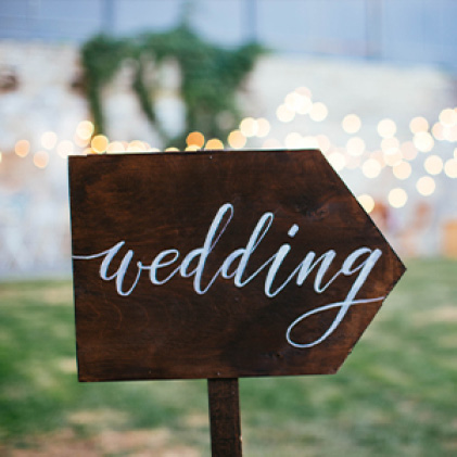 "Arrow-shaped chalkboard sign that reads ""Wedding"""